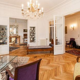 トゥールーズの大きいヴィクトリアン調のおしゃれなファミリールーム (白い壁、淡色無垢フローリング、標準型暖炉、木材の暖炉まわり) の写真