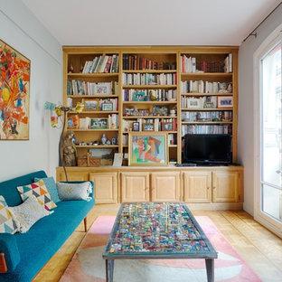 Idée de décoration pour une salle de séjour avec une bibliothèque ou un coin lecture bohème avec un mur gris, un sol en bois clair, un téléviseur encastré et un sol beige.