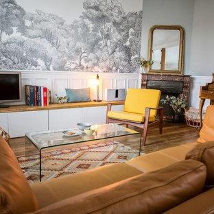 Esempio di un piccolo soggiorno minimal aperto con libreria, pareti blu, parquet chiaro, camino ad angolo, cornice del camino in pietra, TV autoportante e pavimento marrone