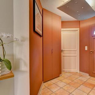 他の地域の大きいコンテンポラリースタイルのおしゃれなファミリールーム (ライブラリー、緑の壁、テラコッタタイルの床、標準型暖炉、金属の暖炉まわり、据え置き型テレビ、茶色い床) の写真