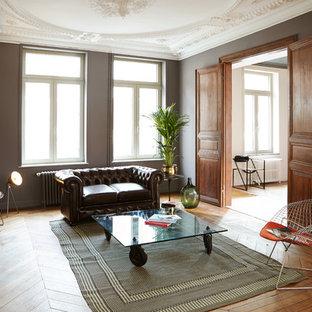 Réalisation d'une grand salle de séjour bohème fermée avec un mur gris, un sol en bois brun, une cheminée standard, un manteau de cheminée en pierre et aucun téléviseur.