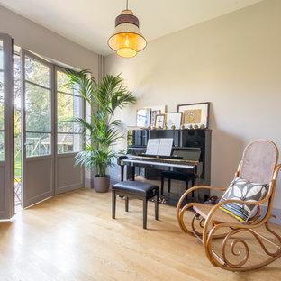 Cette photo montre une salle de séjour chic de taille moyenne et fermée avec une salle de musique, un mur blanc, un sol en bois clair, aucune cheminée, aucun téléviseur et un sol beige.