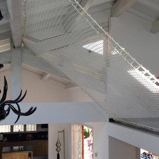 ニースの大きいコンテンポラリースタイルのおしゃれなオープンリビング (ゲームルーム、白い壁、リノリウムの床、薪ストーブ、据え置き型テレビ、グレーの床) の写真