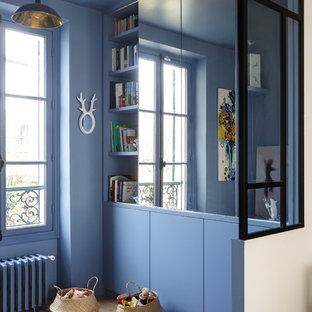 他の地域の中サイズのコンテンポラリースタイルのおしゃれなファミリールーム (ライブラリー、青い壁、淡色無垢フローリング、内蔵型テレビ、ベージュの床、暖炉なし) の写真