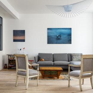 Réalisation d'une salle de séjour nordique ouverte avec un mur blanc, un sol en bois clair et aucune cheminée.
