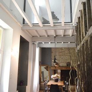 Imagen de sala de estar tipo loft, campestre, de tamaño medio, con paredes blancas, suelo de baldosas de terracota, chimenea tradicional, marco de chimenea de piedra y suelo rojo