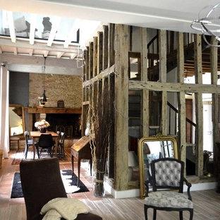 他の地域の大きいコンテンポラリースタイルのおしゃれなファミリールーム (白い壁、テラコッタタイルの床、標準型暖炉、石材の暖炉まわり、赤い床) の写真