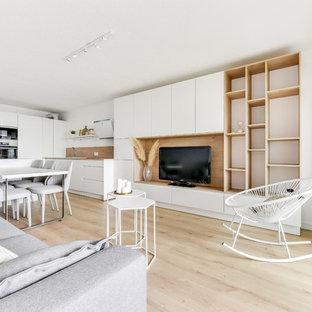 モンペリエの中サイズのビーチスタイルのおしゃれなファミリールーム (ライブラリー、白い壁、ラミネートの床、据え置き型テレビ、茶色い床) の写真