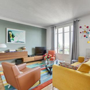 Cette image montre une salle de séjour design de taille moyenne et ouverte avec un sol en bois clair, un téléviseur indépendant, un sol marron, un mur vert et aucune cheminée.