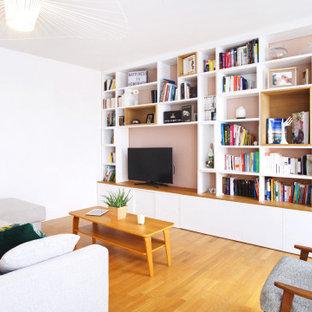 Aménagement d'une grand salle de séjour contemporaine ouverte avec un mur beige, un sol en bois clair, aucune cheminée, un téléviseur encastré et un sol marron.