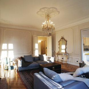 Cette image montre une grand salle de séjour traditionnelle fermée avec un mur beige, un sol en bois brun, une cheminée standard, un manteau de cheminée en pierre, aucun téléviseur et un sol marron.