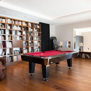 Idées déco pour une grande salle de séjour avec une bibliothèque ou un coin lecture rétro ouverte avec un mur blanc et un sol en bois clair.