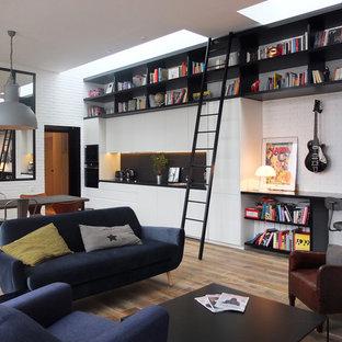 Industriell inredning av ett mellanstort allrum med öppen planlösning, med ett musikrum, vita väggar och ljust trägolv