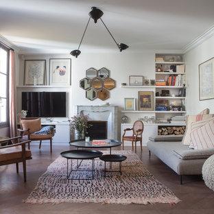 Idées déco pour une salle de séjour avec une bibliothèque ou un coin lecture classique ouverte avec un mur blanc, une cheminée standard, un téléviseur fixé au mur et un sol marron.
