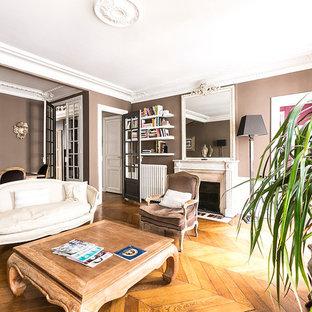 Inspiration pour une grande salle de séjour avec une bibliothèque ou un coin lecture traditionnelle ouverte avec un mur beige, un sol en bois brun, une cheminée standard, un manteau de cheminée en pierre et aucun téléviseur.