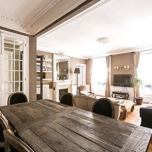 Cette photo montre une grande salle de séjour avec une bibliothèque ou un coin lecture chic ouverte avec un mur beige, un sol en bois brun, une cheminée standard, un manteau de cheminée en pierre et un téléviseur fixé au mur.