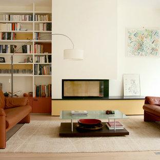 Inspiration pour une grand salle de séjour avec une bibliothèque ou un coin lecture design ouverte avec un mur blanc, un sol en bois clair et aucun téléviseur.