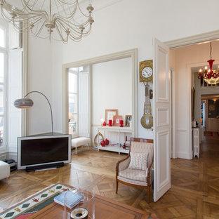 Cette photo montre une salle de séjour chic ouverte avec un mur blanc, un sol en bois brun et un téléviseur indépendant.
