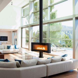 Exemple d'une grande salle de séjour tendance ouverte avec un mur blanc, un sol en bois clair, un téléviseur fixé au mur et une cheminée ribbon.