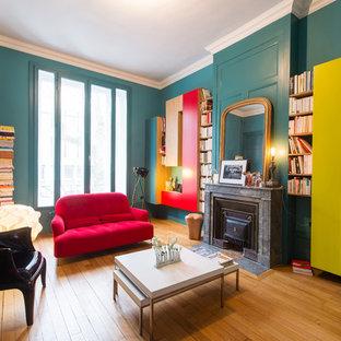 Idées déco pour une salle de séjour avec une bibliothèque ou un coin lecture contemporaine de taille moyenne et fermée avec un mur bleu, un sol en bois brun, une cheminée standard et un manteau de cheminée en pierre.