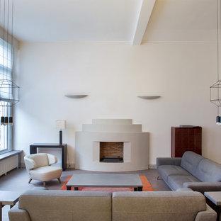 Idée de décoration pour une grande salle de séjour design fermée avec un mur beige, une cheminée standard, un manteau de cheminée en plâtre et un téléviseur indépendant.