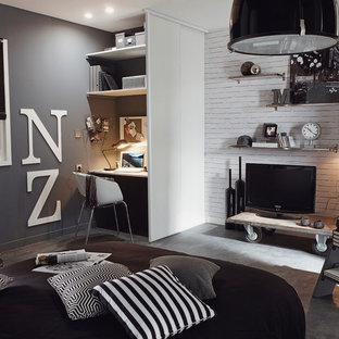 Inspiration pour une salle de séjour avec une bibliothèque ou un coin lecture design de taille moyenne et ouverte avec un mur gris, béton au sol, aucune cheminée et un téléviseur indépendant.