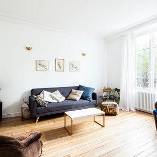 Cette image montre une salle de séjour nordique ouverte avec un mur blanc et un sol en bois clair.