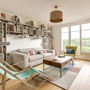 Cette image montre une salle de séjour avec une bibliothèque ou un coin lecture design ouverte avec un mur blanc, un sol en bois clair et un sol beige.