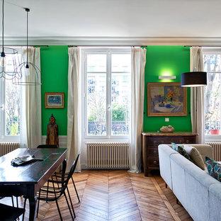Idée de décoration pour une grande salle de séjour avec une bibliothèque ou un coin lecture bohème ouverte avec un mur vert, un sol en bois brun, aucune cheminée et un téléviseur encastré.