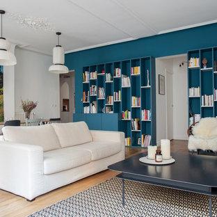 Aménagement d'une salle de séjour avec une bibliothèque ou un coin lecture contemporaine de taille moyenne et ouverte avec un mur bleu, un sol en bois clair, aucune cheminée et aucun téléviseur.