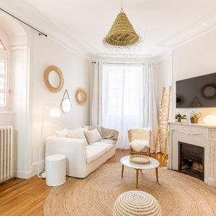 Inspiration pour une salle de séjour marine avec un mur blanc, un sol en bois brun, une cheminée standard, un téléviseur fixé au mur et un sol marron.