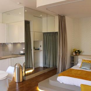 Imagen de sala de estar abierta, contemporánea, pequeña, con paredes blancas, suelo de madera en tonos medios, chimenea tradicional y marco de chimenea de piedra