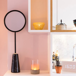 Diseño de sala de estar con biblioteca abierta, contemporánea, pequeña, sin chimenea, con paredes rosas, suelo de madera clara, pared multimedia y suelo marrón