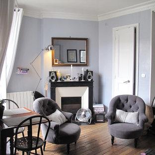 Modelo de sala de estar cerrada, tradicional renovada, pequeña, sin televisor, con suelo de madera en tonos medios, chimenea tradicional, marco de chimenea de piedra y paredes púrpuras