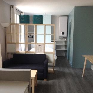 Foto de sala de estar abierta, contemporánea, pequeña, sin chimenea y televisor, con paredes azules, suelo vinílico y suelo gris