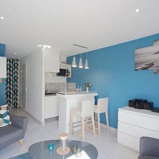 Foto de sala de estar abierta, contemporánea, pequeña, sin chimenea, con paredes azules, suelo de linóleo y televisor independiente