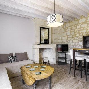 Inspiration pour une salle de séjour méditerranéenne avec un mur beige, un sol en bois brun, une cheminée d'angle, un téléviseur indépendant et un sol marron.