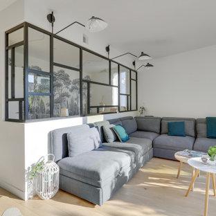 Esempio di un grande soggiorno moderno aperto con libreria, pareti verdi, parquet chiaro, camino sospeso, cornice del camino in intonaco, pavimento marrone e carta da parati