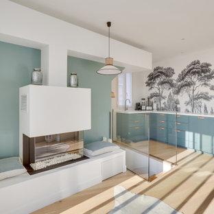 Große, Offene Moderne Bibliothek mit grüner Wandfarbe, hellem Holzboden, Hängekamin, verputzter Kaminumrandung, braunem Boden und Tapetenwänden in Paris