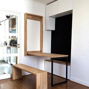 Imagen de sala de estar abierta, actual, pequeña, con suelo de madera clara y chimenea tradicional