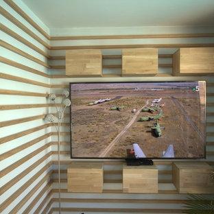 パリの中サイズのコンテンポラリースタイルのおしゃれなファミリールーム (青い壁、ラミネートの床、壁掛け型テレビ、茶色い床) の写真
