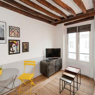 Cette image montre une salle de séjour design de taille moyenne et ouverte avec un mur multicolore, un téléviseur indépendant, un sol en bois brun et un sol beige.