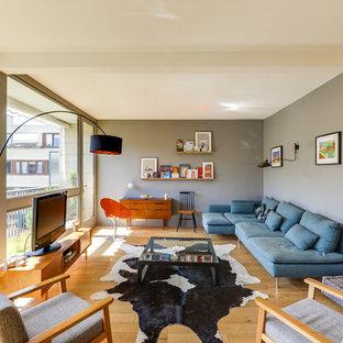 Inspiration pour une salle de séjour avec une bibliothèque ou un coin lecture design avec un mur gris, un sol en bois clair et aucune cheminée.