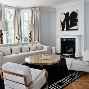 Large classic enclosed family and games room in London with grey walls, a standard fireplace, a stone fireplace surround, medium hardwood flooring and brown floors.