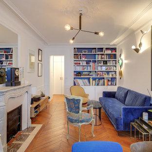 Exemple d'une salle de séjour chic avec un mur blanc, un sol en bois brun, une cheminée standard et un sol marron.