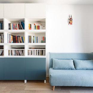 Aménagement d'une salle de séjour avec une bibliothèque ou un coin lecture contemporaine de taille moyenne avec un mur blanc, un sol en bois clair, aucune cheminée et un sol beige.