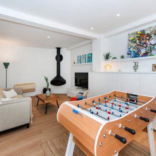 Aménagement d'une salle de séjour scandinave avec salle de jeu, un mur blanc, un sol en bois clair, cheminée suspendue, un téléviseur indépendant et un sol beige.