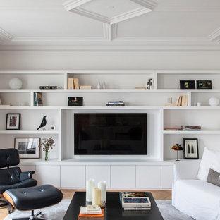 Exemple d'une salle de séjour tendance avec un mur blanc, un téléviseur encastré, un sol en bois clair et aucune cheminée.