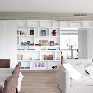 Idées déco pour une salle de séjour avec une bibliothèque ou un coin lecture contemporaine ouverte et de taille moyenne avec un mur blanc et un sol en bois clair.
