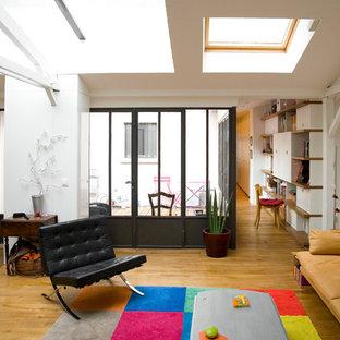 Cette photo montre une salle de séjour industrielle de taille moyenne et ouverte avec un mur blanc, un sol en bois brun et aucun téléviseur.